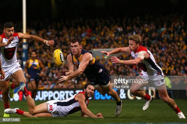 Luke Shuey of the Eagles handballs during the round 14 AFL match between the West Coast Eagles and the Melbourne Demons at Domain Stadium on June 24...