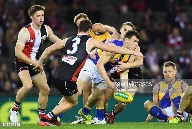 Luke Shuey of the Eagles handballs whilst being tackled during the round 20 AFL match between the St Kilda Saints and the West Coast Eagles at Etihad...