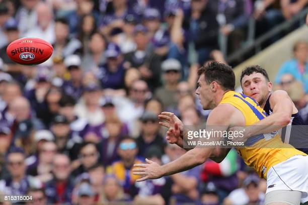 Luke Shuey of the Eagles handpasses the ball under pressure from Hayden Ballantyne of the Dockers during the round 17 AFL match between the Fremantle...