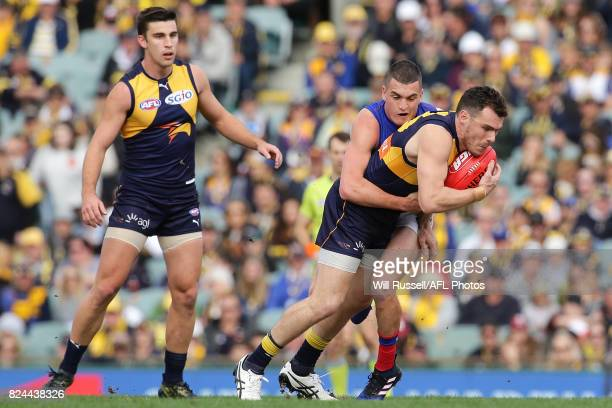 Luke Shuey of the Eagles is tackled by Tom Rockliff of the Lions during the round 19 AFL match between the West Coast Eagles and the Brisbane Lions...