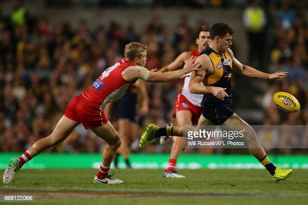 Luke Shuey of the Eagles kicks the ball under pressure from Dan Hannebery of the Swans during the round four AFL match between the West Coast Eagles...