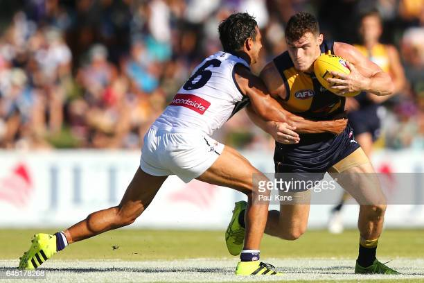 Luke Shuey of the Eagles looks to break from a tackle by Danyle Pearce of the Dockers during the JLT Community Series AFL match between the West...