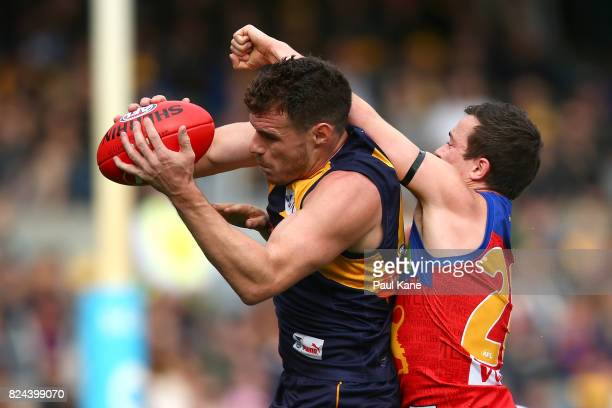 Luke Shuey of the Eagles marks the ball against Lewis Taylor of the Lions during the round 19 AFL match between the West Coast Eagles and the...