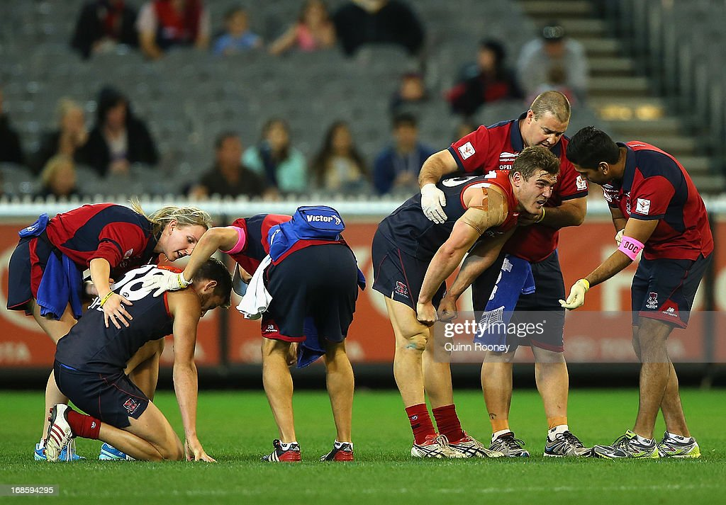 Luke Tapscott and Jeremy Howe of the Demons are attended to by trainers after colliding with each other during the round seven AFL match between the Melbourne Demons and the Gold Coast Suns at Melbourne Cricket Ground on May 12, 2013 in Melbourne, Australia.