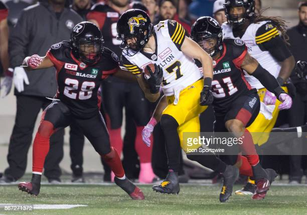 Luke Tasker of the Hamilton TigerCats gets ready to be tackled by Corey Tindal of the Ottawa Redblacks in Canadian Football League play at TD Place...