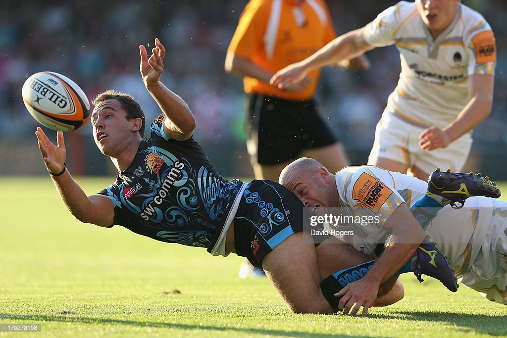 Luke Treharne of Exeter Chiefs off loads the ball as <a gi-track='captionPersonalityLinkClicked' href=/galleries/search?phrase=Paul+Hodgson&family=editorial&specificpeople=624967 ng-click='$event.stopPropagation()'>Paul Hodgson</a> of Worcester Warriors tackles during the J.P. Morgan Asset Management Premiership Rugby 7's held at Kingsholm Stadium on August 1, 2013 in Gloucester, England.