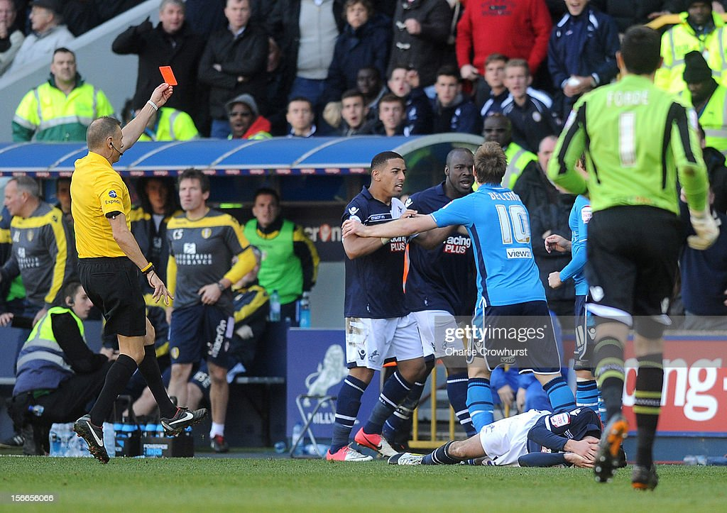 Luke Varney (obscured) of Leeds is sent off by referee <a gi-track='captionPersonalityLinkClicked' href=/galleries/search?phrase=Mark+Halsey&family=editorial&specificpeople=224397 ng-click='$event.stopPropagation()'>Mark Halsey</a> for a foul on <a gi-track='captionPersonalityLinkClicked' href=/galleries/search?phrase=Adam+Smith+-+Calciatore+-+Terzino+destro&family=editorial&specificpeople=14054674 ng-click='$event.stopPropagation()'>Adam Smith</a> of Millwall, who lies injured on the ground during the npower Championship match between Millwall and Leeds United at The New Den on November 18, 2012 in London, England.