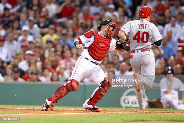 Luke Voit of the St Louis Cardinals scores a run past Christian Vazquez of the Boston Red Sox during the second inning at Fenway Park on August 16...