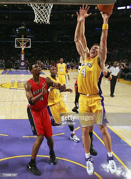 Luke Walton of the Los Angeles Lakers drives to the basket past Chris Bosh of the Toronto Raptors during the first half of the game on November 17...