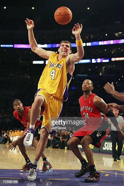 Luke Walton of the Los Angeles Lakers loses control of the ball while driving to the basket past Morris Peterson of the Toronto Raptors during the...
