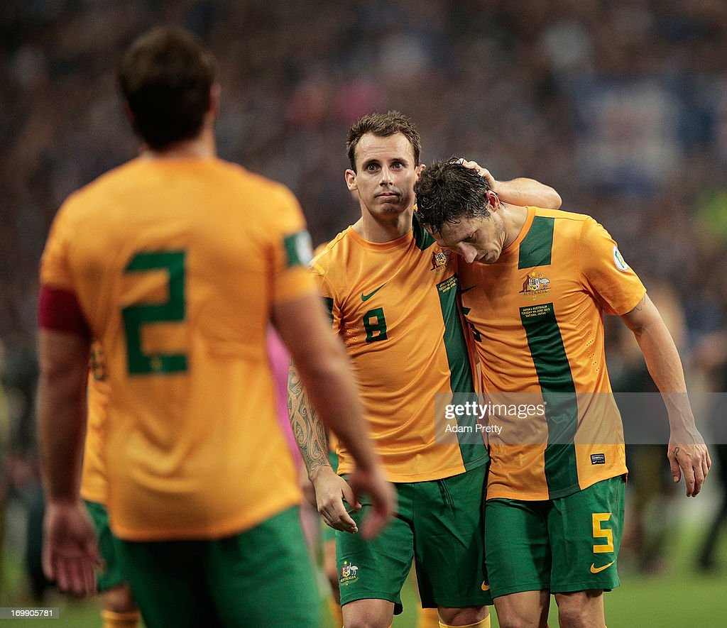 Luke Wilkshire and Mark Milligan of Australia are dejected after the FIFA World Cup qualifier match between Japan and Australia at Saitama Stadium on June 4, 2013 in Saitama, Japan.