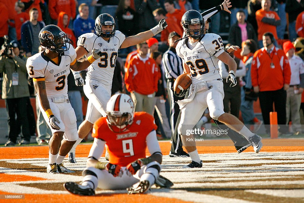 Luke Wollet #39, Leon Green #3, and Luke Batton #30, all of the Kent State Golden Flashes, celebrates after Wollet intercepted a pass intended for Shaun Joplin #9 of the Bowling Green Falcons in the fourth quarter on November 17, 2012 at Doyt Perry Stadium in Bowling Green, Ohio. Kent State defeated Bowling Green 31-24.
