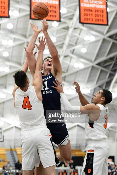 Luke Worthington of the Brigham Young Cougars is guarded by Mike LeBlanc of the Princeton Tigers and teammate Devin Cannady during the first half at...