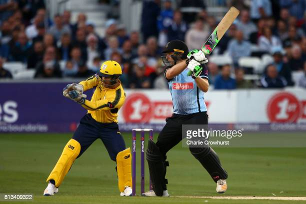 Luke Wright of Sussex hits out while Hampshire's wicket keeper Lewis McManus looks on during the NatWest T20 Blast match between Sussex Sharks and...