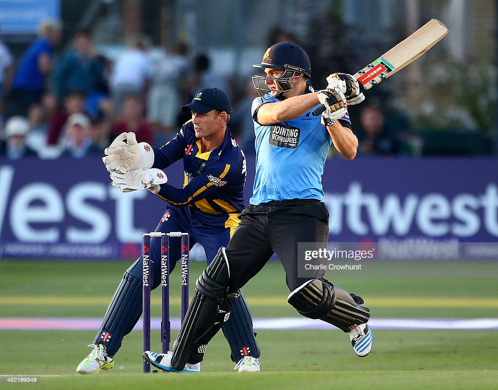 Luke Wright of Sussex hits out while Mark Wallace of Glamorgan looks on during the Natwest T20 Blast match between Sussex Sharks and Glamorgan at The BrightonAndHoveJobs.com County Ground on July 15, 2014 in Hove, England.