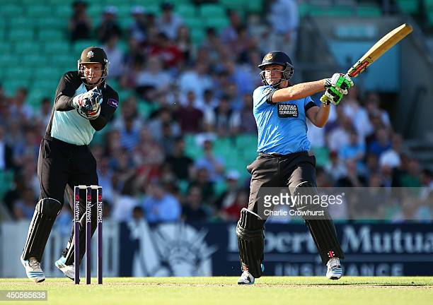 Luke Wright of Sussex hits out while Surrey's Gary Wilson looks on during the Natwest T20 Blast match between Surrey and Sussex Sharks at The Kia...