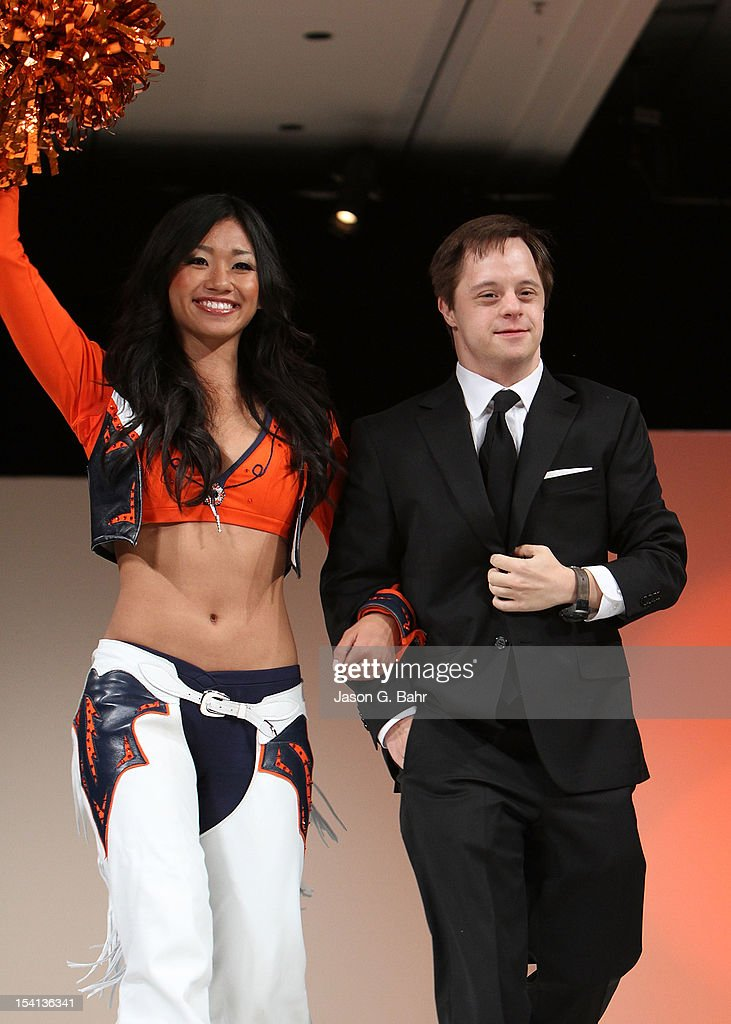 Luke Zimmerman (R) is accompanied by a Denver Broncos cheerleader on the runway during the Be Beautiful Be Yourself Fashion Show at Sheraton Downtown Denver Hotel on October 13, 2012 in Denver, Colorado.