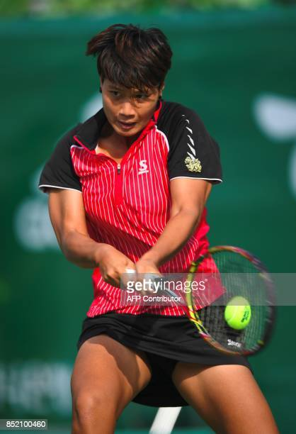 Luksika Kumkhum of Thailand hits a return against Jelena Ostapenko of Latvia during their women's singles semifinal match at the WTA Korea Open...