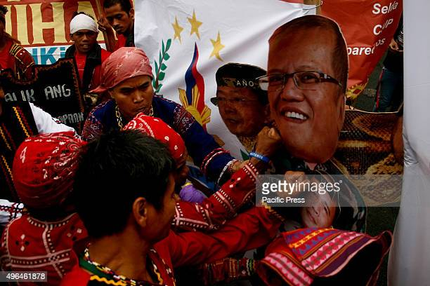 Lumads punch a cardboard standee of the President of the Philippines Benigno Aquino III and the generals of the AFP Hundreds of 'Lumad' marched to...