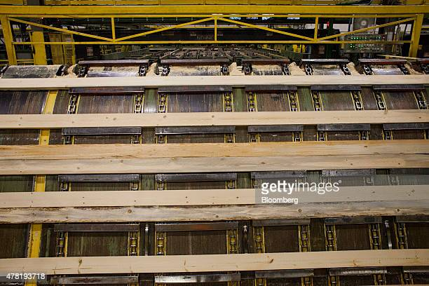 Lumber moves along a conveyor belt during processing at the West Fraser Timber Co sawmill in Quesnel British Columbia Canada on Friday June 5 2015...