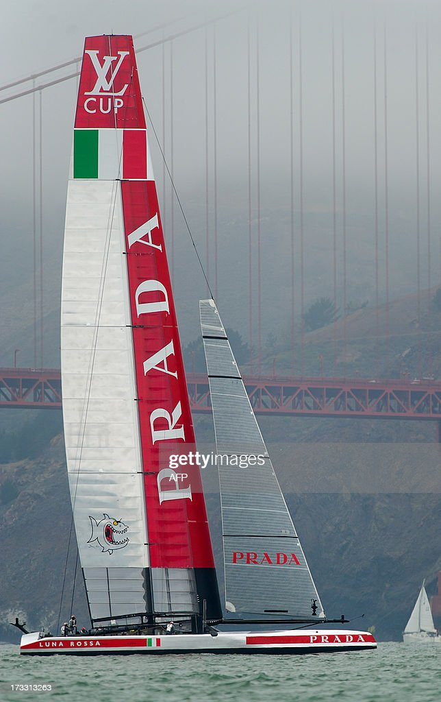 Luna Rossa Challenge dwarfs a sailboat as is passes the Golden Gate Bridge before sailing the Louis Vuitton Cup circuit for points on July 11, 2013, in San Francisco. Originally slated to compete against Artemis Racing, Luna Rossa sailed the course alone as Artemis recovers from a May 9 accident that left it without a ready AC72 catamaran.