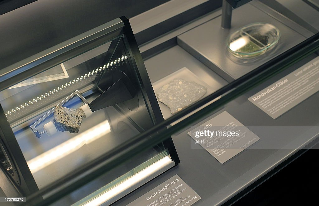 A lunar basalt rock (L), a slice of a lunar meteorite stone (C) and lunar volcanic glasses (R) are displayed at the Meteorite room of the Natural History Museum (Naturhistorisches Museum Wien NHM) in Vienna on June 18, 2013. The approx. 84 grams (2.96 Oz) basalt stone and items are displayed at the museum and where brought during the 'Apollo 15' mission in 1971.