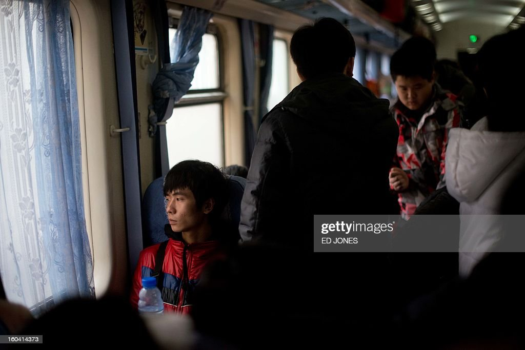 A Lunar New Year traveller (L) looks from the window of a train bound for the southwestern Chinese city of Chongqing, a journey of 32 hours, as it departs from the West Railway Station in Beijing on January 31, 2013. The world's largest annual migration is underway in China with tens of millions across China boarding trains to journey home for Lunar New Year celebrations. Passengers will log 220 million train rides during the 40-day travel season as they criss-cross the country to celebrate with their families on February 10, but just as making the trip home can be laborious -- often lasting one or two days -- so can simply acquiring a seat on the train, and every year complaints arise about the inefficiency or unfairness of the system, although an initiative allowing travelers to purchase tickets online aims to curb long queuing times. AFP PHOTO / Ed Jones