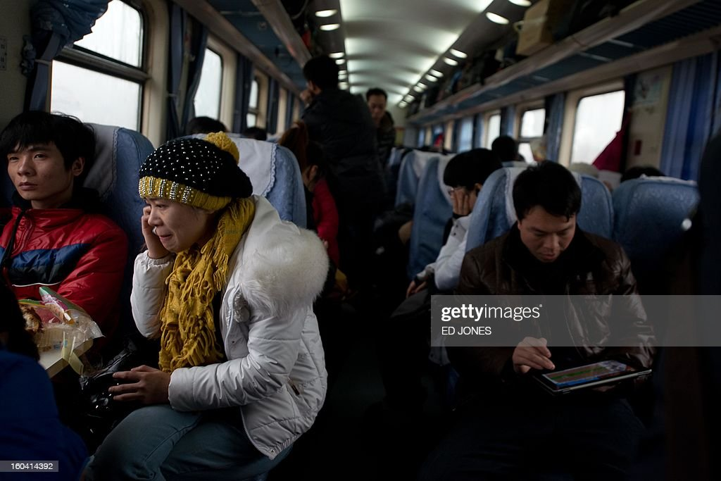 A Lunar New Year traveller (2nd L) talks on a mobile phone aboard train bound for the southwestern Chinese city of Chongqing, a journey of 32 hours, after departing from the West Railway Station in Beijing on January 31, 2013. The world's largest annual migration is underway in China with tens of millions across China boarding trains to journey home for Lunar New Year celebrations. Passengers will log 220 million train rides during the 40-day travel season as they criss-cross the country to celebrate with their families on February 10, but just as making the trip home can be laborious -- often lasting one or two days -- so can simply acquiring a seat on the train, and every year complaints arise about the inefficiency or unfairness of the system, although an initiative allowing travelers to purchase tickets online aims to curb long queuing times. AFP PHOTO / Ed Jones