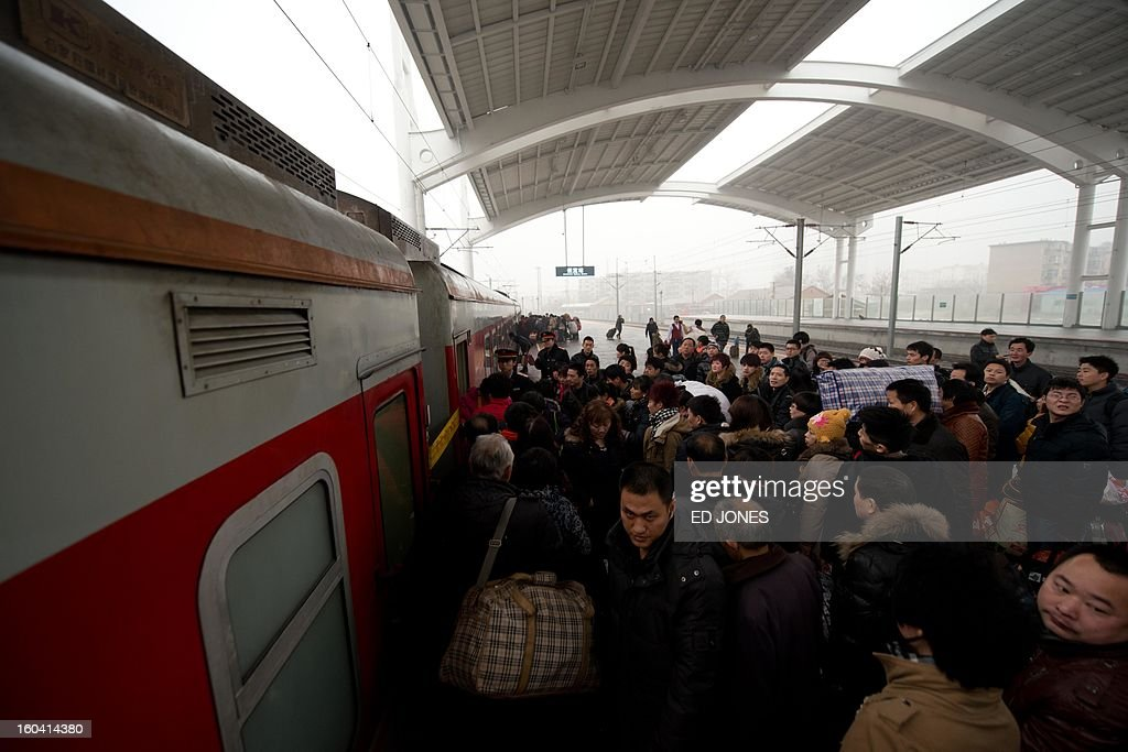 Lunar New Year travellers board a train bound for the southwestern Chinese city of Chongqing, a journey of 32 hours, at the Baoding railway station in in Hebei Province, south of Beijing on January 31, 2013. The world's largest annual migration is underway in China with tens of millions across China boarding trains to journey home for Lunar New Year celebrations. Passengers will log 220 million train rides during the 40-day travel season as they criss-cross the country to celebrate with their families on February 10, but just as making the trip home can be laborious -- often lasting one or two days -- so can simply acquiring a seat on the train, and every year complaints arise about the inefficiency or unfairness of the system, although an initiative allowing travelers to purchase tickets online aims to curb long queuing times. AFP PHOTO / Ed Jones