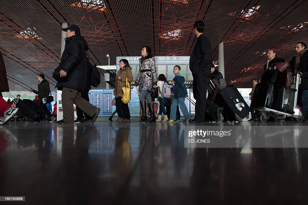 Lunar New Year travellers crowd the terminal at Beijing's international airport on February 6, 2013. China is preparing to welcome the Lunar New Year, or Spring Festival, which falls on Febraury 10. AFP PHOTO / Ed Jones