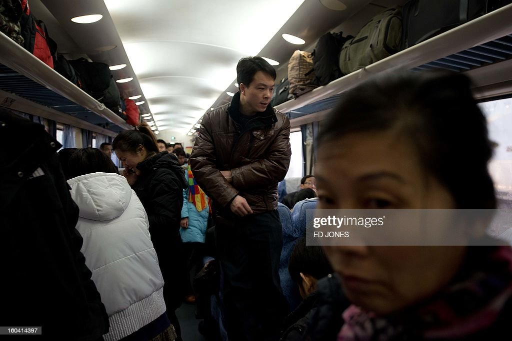 Lunar New Year travellers look for seats aboard a crowded train bound for the southwestern Chinese city of Chongqing, a journey of 32 hours, at the West Railway Station in Beijing on January 31, 2013. The world's largest annual migration is underway in China with tens of millions across China boarding trains to journey home for Lunar New Year celebrations. Passengers will log 220 million train rides during the 40-day travel season as they criss-cross the country to celebrate with their families on February 10, but just as making the trip home can be laborious -- often lasting one or two days -- so can simply acquiring a seat on the train, and every year complaints arise about the inefficiency or unfairness of the system, although an initiative allowing travelers to purchase tickets online aims to curb long queuing times. AFP PHOTO / Ed Jones