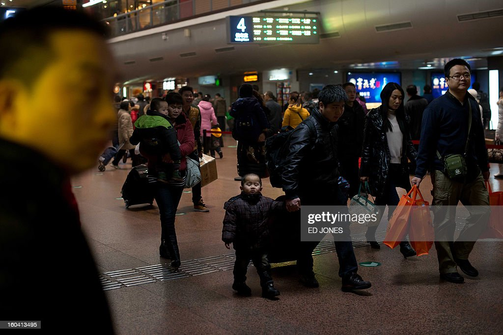 Lunar New Year travellers make their way through the West Railway Station in Beijing on January 31, 2013. The world's largest annual migration is underway in China with tens of millions across China boarding trains to journey home for Lunar New Year celebrations. Passengers will log 220 million train rides during the 40-day travel season as they criss-cross the country to celebrate with their families on February 10, but just as making the trip home can be laborious -- often lasting one or two days -- so can simply acquiring a seat on the train, and every year complaints arise about the inefficiency or unfairness of the system, although an initiative allowing travelers to purchase tickets online aims to curb long queuing times. AFP PHOTO / Ed Jones