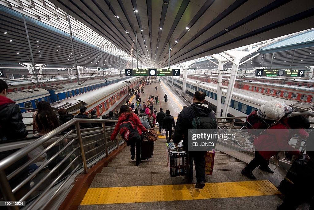 Lunar New Year travellers make their way to a waiting train bound for the southwestern Chinese city of Chongqing, a journey of 32 hours, at the West Railway Station in Beijing on January 31, 2013. The world's largest annual migration is underway in China with tens of millions across China boarding trains to journey home for Lunar New Year celebrations. Passengers will log 220 million train rides during the 40-day travel season as they criss-cross the country to celebrate with their families on February 10, but just as making the trip home can be laborious -- often lasting one or two days -- so can simply acquiring a seat on the train, and every year complaints arise about the inefficiency or unfairness of the system, although an initiative allowing travelers to purchase tickets online aims to curb long queuing times. AFP PHOTO / Ed Jones