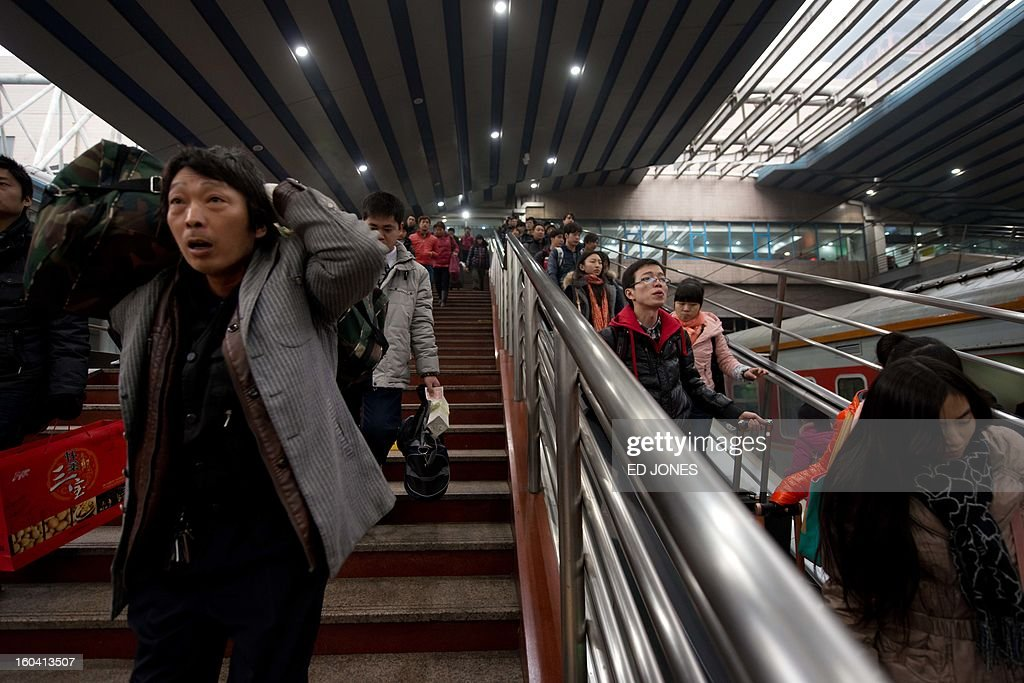 Lunar New Year travellers make their way to a waiting train bound for the south-western Chinese city of Chongqing, a journey of 32 hours, at the West Railway Station in Beijing on January 31, 2013. The world's largest annual migration is underway in China with tens of millions across China boarding trains to journey home for Lunar New Year celebrations. Passengers will log 220 million train rides during the 40-day travel season as they criss-cross the country to celebrate with their families on February 10, but just as making the trip home can be laborious -- often lasting one or two days -- so can simply acquiring a seat on the train, and every year complaints arise about the inefficiency or unfairness of the system, although an initiative allowing travelers to purchase tickets online aims to curb long queuing times. AFP PHOTO / Ed Jones