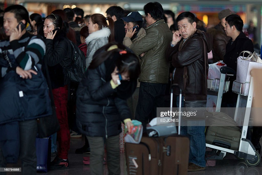Lunar New Year traveLlers queue at Beijing's international airport on February 6, 2013. China is preparing to welcome the Lunar New Year, or Spring Festival, which falls on Febraury 10. AFP PHOTO / Ed Jones