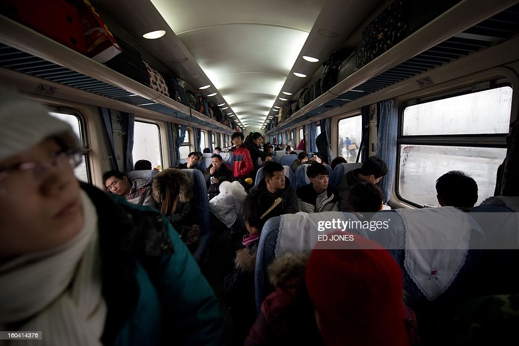 Lunar New Year travellers sit aboard a crowded train bound for the southwestern Chinese city of Chongqing, a journey of 32 hours, after departing from the West Railway Station in Beijing on January 31, 2013. The world's largest annual migration is underway in China with tens of millions across China boarding trains to journey home for Lunar New Year celebrations. Passengers will log 220 million train rides during the 40-day travel season as they criss-cross the country to celebrate with their families on February 10, but just as making the trip home can be laborious -- often lasting one or two days -- so can simply acquiring a seat on the train, and every year complaints arise about the inefficiency or unfairness of the system, although an initiative allowing travelers to purchase tickets online aims to curb long queuing times. AFP PHOTO / Ed Jones