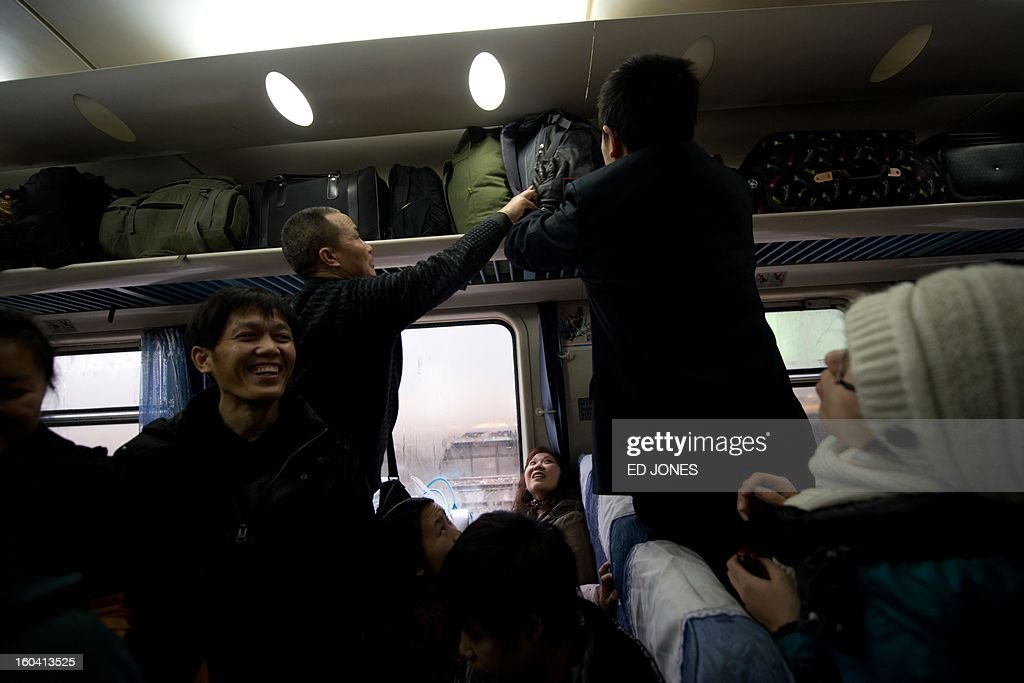 Lunar New Year travellers stow their luggage aboard a train bound for the southwestern Chinese city of Chongqing, a journey of 32 hours, at the West Railway Station in Beijing on January 31, 2013. The world's largest annual migration is underway in China with tens of millions across China boarding trains to journey home for Lunar New Year celebrations. Passengers will log 220 million train rides during the 40-day travel season as they criss-cross the country to celebrate with their families on February 10, but just as making the trip home can be laborious -- often lasting one or two days -- so can simply acquiring a seat on the train, and every year complaints arise about the inefficiency or unfairness of the system, although an initiative allowing travelers to purchase tickets online aims to curb long queuing times. AFP PHOTO / Ed Jones