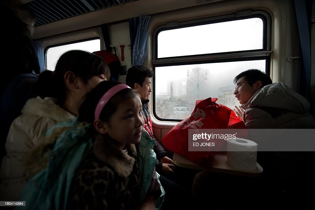 Lunar New Year travellers talk as they sit aboard a train bound for the southwestern Chinese city of Chongqing, a journey of 32 hours, as it departs the West Railway Station in Beijing on January 31, 2013. The world's largest annual migration is underway in China with tens of millions across China boarding trains to journey home for Lunar New Year celebrations. Passengers will log 220 million train rides during the 40-day travel season as they criss-cross the country to celebrate with their families on February 10, but just as making the trip home can be laborious -- often lasting one or two days -- so can simply acquiring a seat on the train, and every year complaints arise about the inefficiency or unfairness of the system, although an initiative allowing travelers to purchase tickets online aims to curb long queuing times. AFP PHOTO / Ed Jones