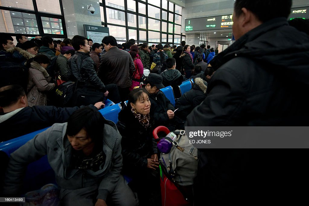 Lunar New Year travellers wait for a train in the West Railway Station in Beijing on January 31, 2013. The world's largest annual migration is underway in China with tens of millions across China boarding trains to journey home for Lunar New Year celebrations. Passengers will log 220 million train rides during the 40-day travel season as they criss-cross the country to celebrate with their families on February 10, but just as making the trip home can be laborious -- often lasting one or two days -- so can simply acquiring a seat on the train, and every year complaints arise about the inefficiency or unfairness of the system, although an initiative allowing travelers to purchase tickets online aims to curb long queuing times. AFP PHOTO / Ed Jones