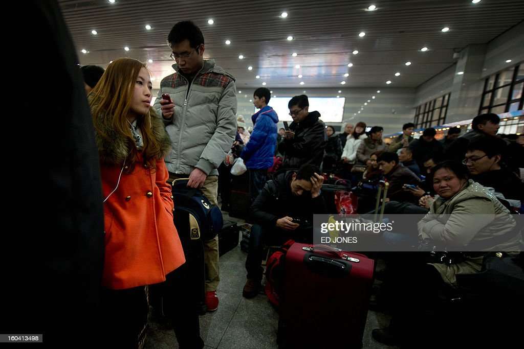 Lunar New Year travellers wait for their train at the West Railway Station in Beijing on January 31, 2013. The world's largest annual migration is underway in China with tens of millions across China boarding trains to journey home for Lunar New Year celebrations. Passengers will log 220 million train rides during the 40-day travel season as they criss-cross the country to celebrate with their families on February 10, but just as making the trip home can be laborious -- often lasting one or two days -- so can simply acquiring a seat on the train, and every year complaints arise about the inefficiency or unfairness of the system, although an initiative allowing travelers to purchase tickets online aims to curb long queuing times. AFP PHOTO / Ed Jones