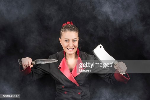 Lunatic maniac female chef holding knife and chopping knife with : Stock Photo