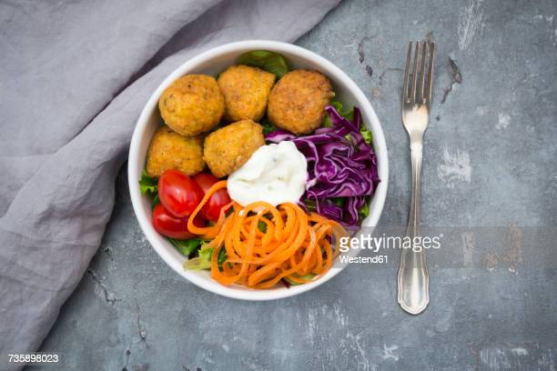 Lunch bowl of leaf salad, red cabbage, tomatoes, carrots, Falafel and yoghurt sauce