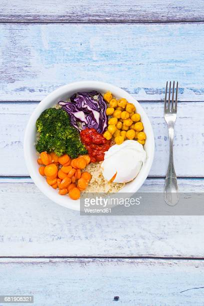 Lunch bowl of quinoa, red cabbage, carrots, roasted chickpeas, broccoli, poached egg and ajvar