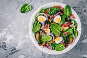 lunch bowl of spinach salad with bacon, mushrooms, eggs and red onions on gray background