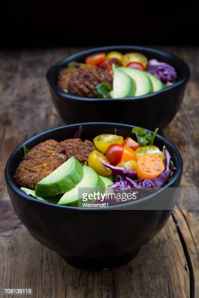Lunch bowls of leaf salad, red cabbage, avocado, tomatoes and quinoa fritters