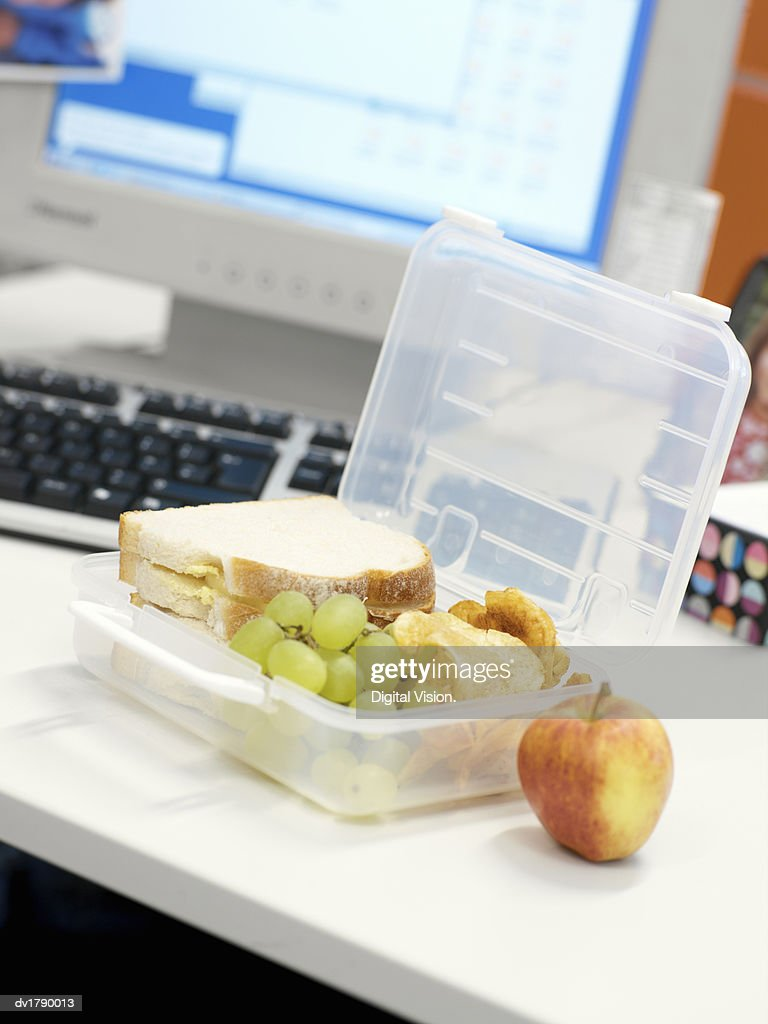 Lunch Box on an Office Desk Containing Sandwiches and Grapes : Stock Photo