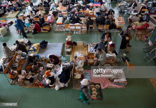 Lunch is served to earthquake victims packed inside an evacuation center where hundreds of homeless are staying March 21 2011 in Rikuzentakata Iwate...
