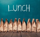 Paper bags in row against blackboard background and word Lunch