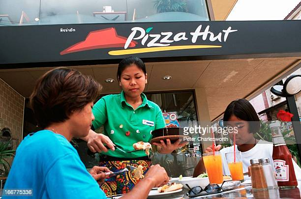 Lunch time customers are served pizza by a Pizza Hut waitress in uniform on the terrace outside a Pizza Hut outlet on the beach road in the holiday...