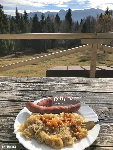 Lunch with nature scenery on the cabin log, ready to eat, bratwurst and sour cabbage.